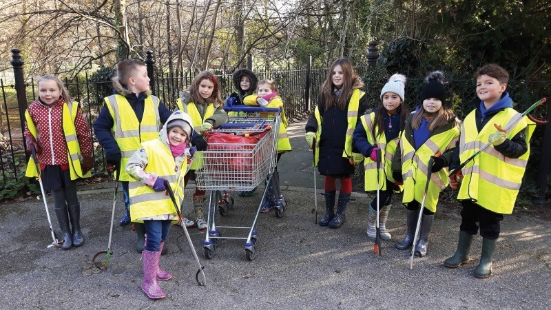 School children in high vis jackets on a litter pick