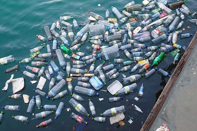 Plastic bottles and food containers floating in a river