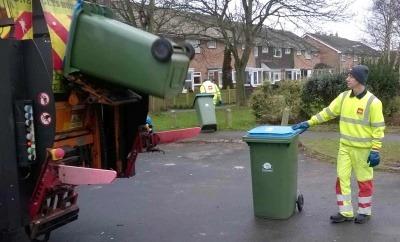 A Biffa employee collects bins.