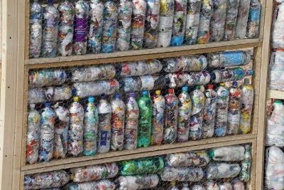 Image of a wall made of waste plastic eco bricks like the ones WasteAid trains communities to make