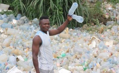 Boy holding plastic bottle in Cameroon