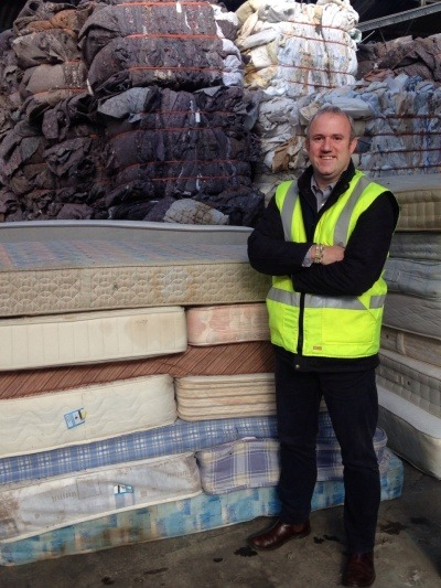Nick Oettinger standing by mattresses ready for recycling
