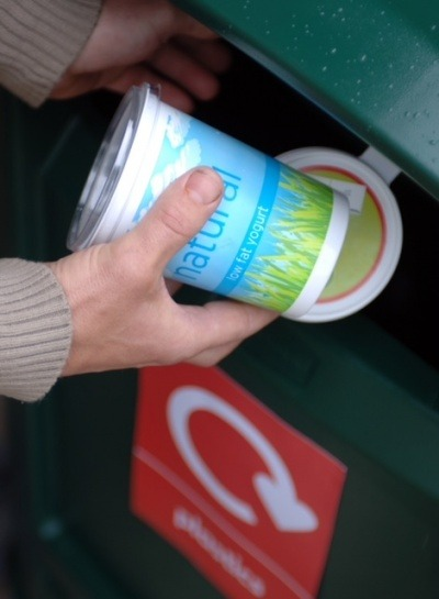 A person putting a plastic pot into a recycling bin