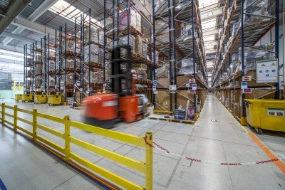 A forklift quickly moving through a warehouse
