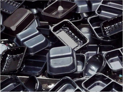 A pile of black plastic food trays