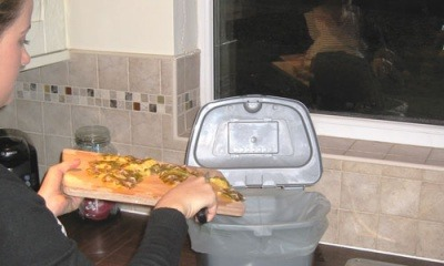 Food waste being scraped into a caddy