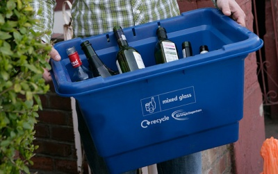 Someone holding a recycling box full of glass bottles
