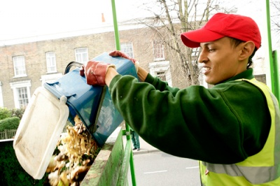 Refuse collector emptying household food waste into lorry