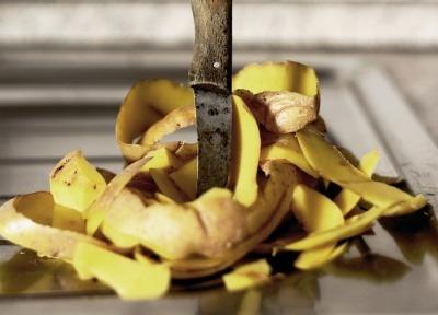 A knife piercing a pile of potato peel