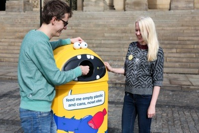 Image of two people using a new recycling bin during the Leeds By Example campaign
