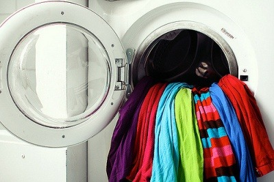 An image of a washing machine with brightly coloured clothing hanging out
