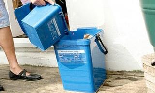 Someone emptying a food waste caddy into their kerbside food bin