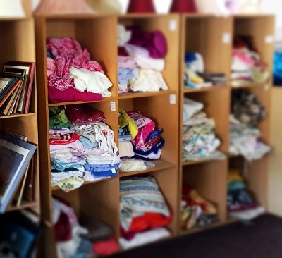 Image of shelves of clothing in a charity shop