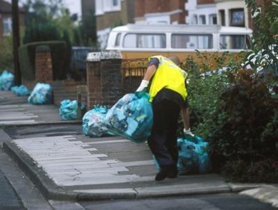 Man picking up kerbside residual bin bags.