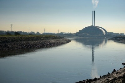 An energy from waste plant in the distance, with a large river and bank in the foreground