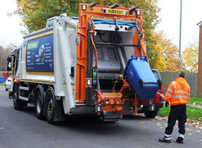 A waste removal vehicle emptying a blue wheelie bin