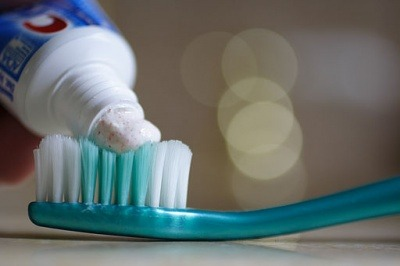 Toothpaste being applied to a toothbrush.