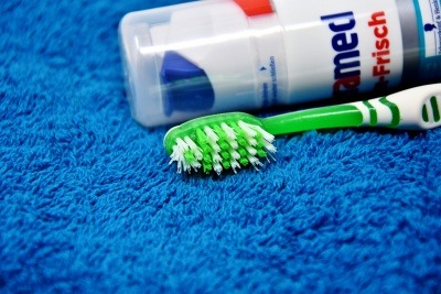 Toothpaste and toothbrush lying on a towel