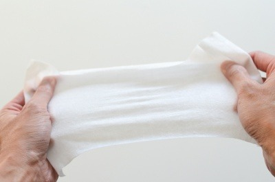 A wet wipe stretched between two hands