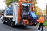 A waste removal truck emptying a wheelie bin