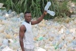 Boy holding plastic bottle in Cameroon