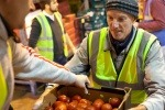 A volunteer passes tomatoes to be redistributed at Fareshare's Yorkshire depot.
