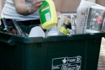 A person placing recycling in a bin