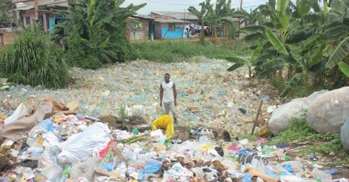 A man stands in the midst of a sea of plastic waste in Cameroon.