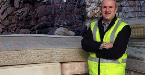 Nick Oettinger standing by mattresses for recycling