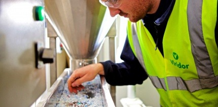 Image of a man in high-vis leaning over a tray of plastic pellets