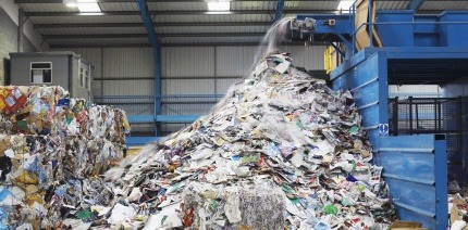 Waste falling from conveyor belt at a recycling facility
