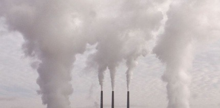Three waste incinerator chimneys pouring out white smoke